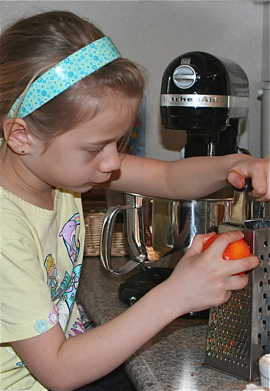 My daughter in the kitchen zesting an orange.